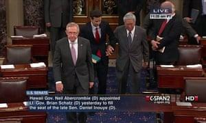 Senate Majority Leader Harry Reid, left, leading Hawaii's Brian Schatz and retiring Hawaii Senator Daniel Akaka, on the Senate floor.