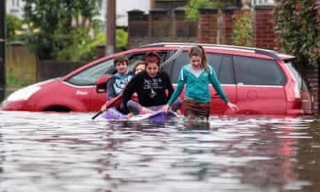 Children make their way down a flooded street in Felpham, West Sussex, in June 2012