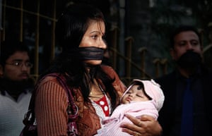 India: An Indian woman ties her mouth with a black cloth and holds her baby