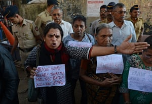 India: An Indian protestor reacts as police officials intervene