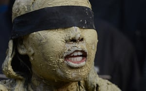 India: An Indian protestor covered in clay