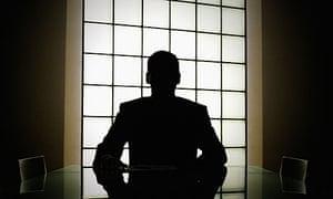 Silhouette of man behind desk