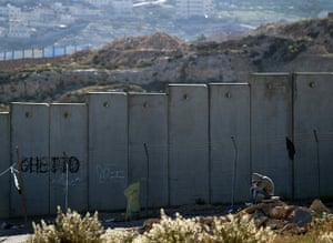 E1 project: A Palestinian sits near the Israeli separation wall in Hizme