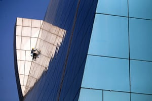 24 hours in pictures: An Indian worker cleans windows of a building
