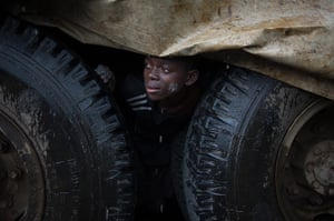 24 hours in pictures: An internally displaced Congolese boy shelters from the rain under a truck