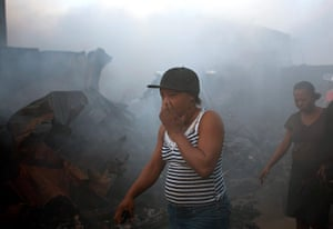 24 hours: A woman covers her mouth and nose as she walks past charred vending stalls