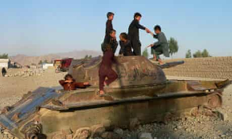 Afghan boys play on the remains of an old Soviet tank