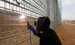 A Sudanese migrant worker works on the construction of the fence between Israel and Egypt