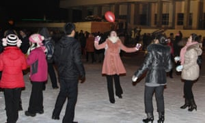 North Koreans in Pyongyang play with a balloon as they wait outside Pyongyang stadium for the countdown to the new year.