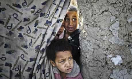 Afghan children wait for winter relief assistance from the UN refugee agency at a camp in Kabul