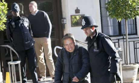 A man wearing a Prince William mask is escorted away from the King Edward VII Private Hospital by a police officer. Catherine, Duchess of Cambridge spent her first night in the hospital after yesterday's announcement of her pregnancy and the fact she was suffering from acute morning sickness.
