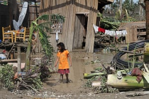 Typhoon Bopha: Children walk in front of their flooded home