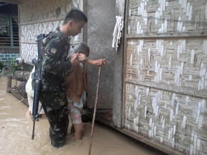 Typhoon Bopha: An elderly woman is assisted by a soldier in Compostela Valley