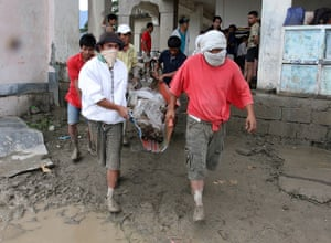 Typhoon Bopha: Rescuers carry a flash flood victim from New Bataan