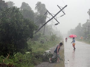 Typhoon Bopha: Residents brave heavy rains next to a tilted electric post in Tagum