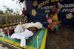 Typhoon Bopha: A man looks at the bodies of relatives killed by landslides