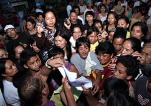 Typhoon Bopha: Residents gather to check the list of supplies at an evacuation centre