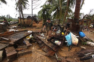 Typhoon Bopha: Residents walk amongst their destroyed houses