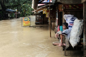 Typhoon Bopha: An elderly woman sits out front of her flooded home in Mabini