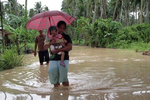 Typhoon Bopha: A woman carrying her child wades through a flooded road in Pantukan town