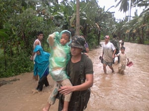 Typhoon Bopha: Philippine Army carries a boy along a flooded area in Compostela Valley