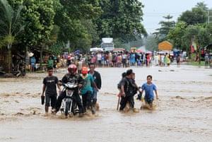 Typhoon Bopha: People cross a flooded road in Mabini