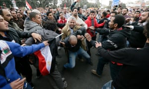 Pro-Morsi supporters beat an opponent during clashes outside the presidential palace, in Cairo, Egypt.