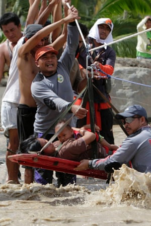 Rescuers evacuate a pregnant woman with her child after surviving flooding in New Bataan town, Compostela Valley, southern Philippines. Rescuers found the women on the other side of the river with her one-year-old son after escaping floods that swamped their house after Typhoon Bopha hit land. The death toll has risen to 332 on Thursday with hundreds missing.