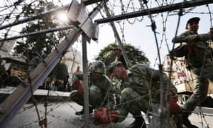 Egyptian Army soldiers install barbed wire near the presidential palace to secure the site of overnight clashes between supporters and opponents of President Mohammed Morsi in Cairo, Egypt. The clashes have left several people dead and hundreds wounded.