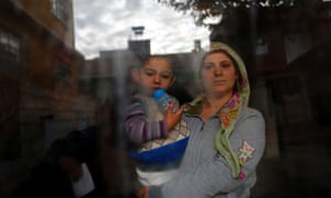 A Syrian refugee holds her son as she stands at the window of her friend's house at the Syrian-Turkish border town of Ceylanpinar.