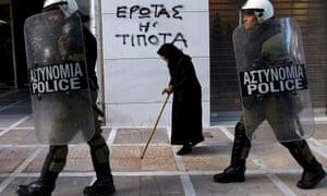 An elderly woman walks past riot police.