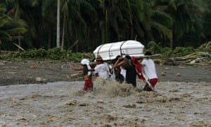 People cross a river with a coffin containing one of the victims of typhoon Bopha in Compostela Valley, Philippines.