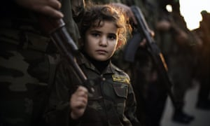 A Palestinian girl dressed as an Ezzedine al-Qassam brigade member is seen holding the barrel of a gun during a march by a Hamas armed wing in Beit Hanun, Gaza Strip.