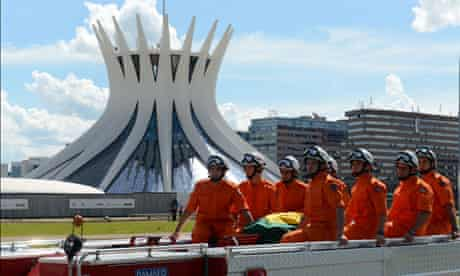 A fire engine escorting Niemayer's coffin passes the Metropolitan Cathedral in Brasilia