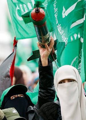 Hamas: A Palestinian woman holds a model of the Qassam rocket