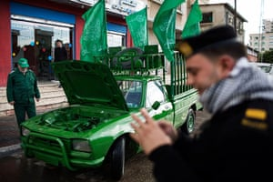 Hamas: A Palestinian Hamas policeman stands next to a vehicle painted green