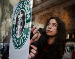 Starbucks: A demonstrator sticks up a protest poster in the window of a Starbucks