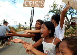 24 hours: Montevista, Philippines: Children beg for food on a street in the typhoon-hit town