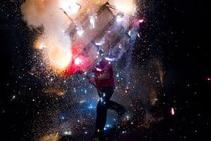 24 hours: Managua, Nicaragua: A man runs with a toro encuetado, a model bull covered in fireworks