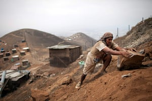 24 hours: Lima, Peru: A man moves a rock as he builds a shack on a mountain top