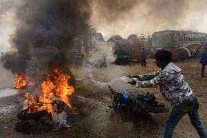 24 hours: Narayanganj, Bangladesh: A man tries to extinguish a burning motorcycle
