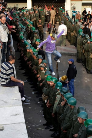 A protester jumps as Egyptian army soldiers stand guard in front of the presidential palace in Cairo, Egypt, Sunday.