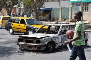 Protest in Senegal: A young Senegalese walks past a car which was burnt after clashes