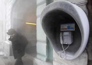 Cold snap continues: A man passes by a city phone, covered with hoarfrost, in Kiev