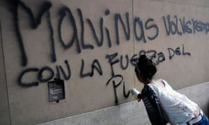 An Argentinian activist sprays graffiti outside the British embassy in Buenos Aires