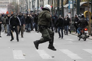 Greece protests: A riot policeman tries to avoid a stone thrown by a protester