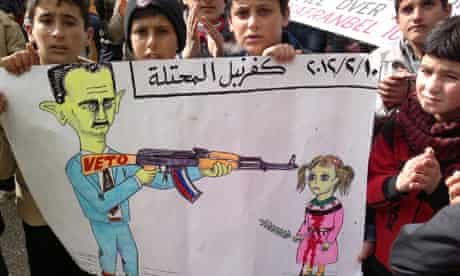 Demonstrators hold a poster during a protest against Syria's President al-Assad