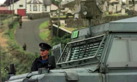 An RUC policeman stands next to an armoured Land Rover in Northern Ireland, 1998