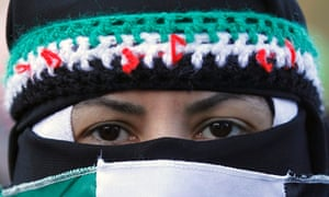 A Syrian woman is masked in the colours of the revolutionary flag during a protest march