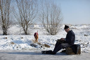 UK weather: A man puts on his ice-skates as he prepares to skate on a frozen fen